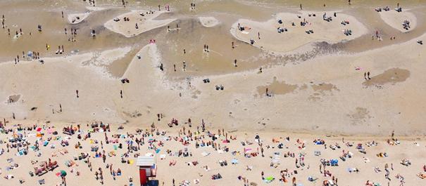 Plaża w Estonii - widok z góry na piaszczystą plażę i bardzo płytkie morze, ludzie opalają się i wchodzą w morze